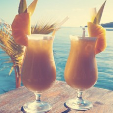 2 cocktails on a table with ocean background. The drinks are on a wooden table with palm trees and water horizon  in the background. Each Pina Colada has a pineapple garnish. Image has lens flare. Cross processed.