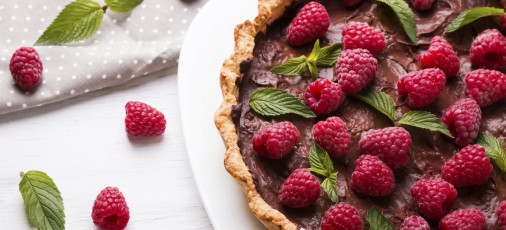 Delicious chocolate tart with raspberry on the white plate